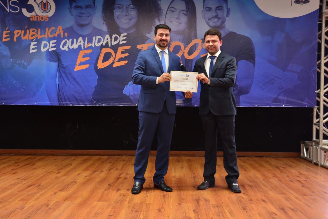 Reitor da Unitins Augusto Rezende entrega homenagem para Carlos Júnior, chefe de gabinete.